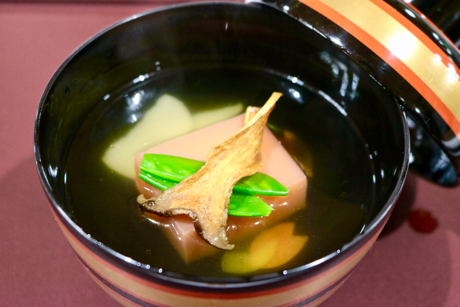 A soup with pink-colored mochi and locally grown vegetables
