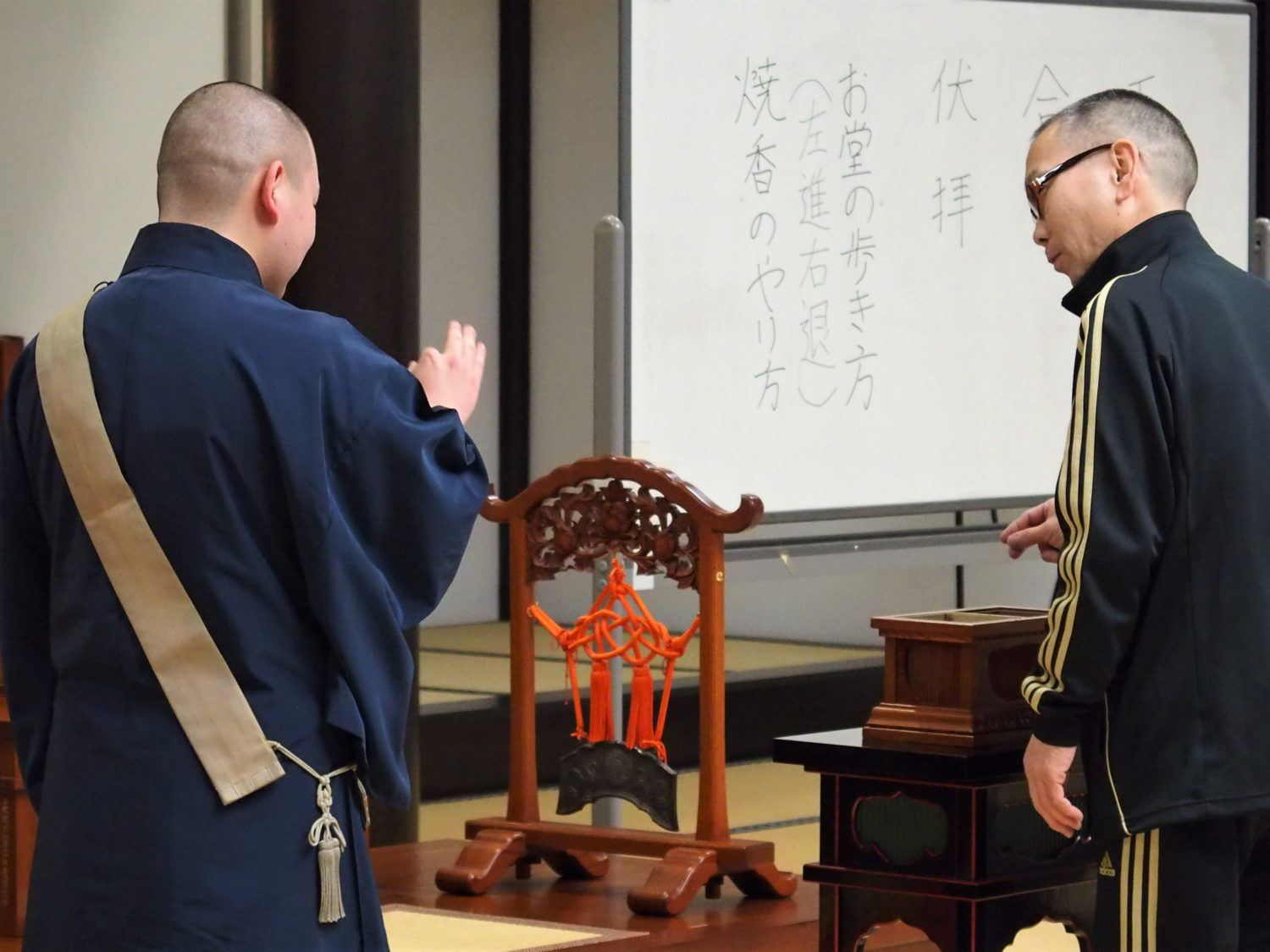 "A Buddhist monk teaching how to ""shoko (offer incense)"""